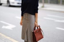 a navy oversized sweater, a tweed midi skirt, black boots and a brown bag for a comfy work outfit