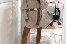 a neutral mini sweater dress, a printed belt, snakeskin boots for a trendy and edgy look