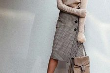 a neutral sweater, a tweed midi skirt with buttons, nude shoes, a tan suede bag for a winter work look