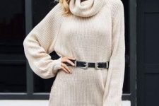 a neutral sweater dress highlighted with a black belt, an amber bag and statement earrings