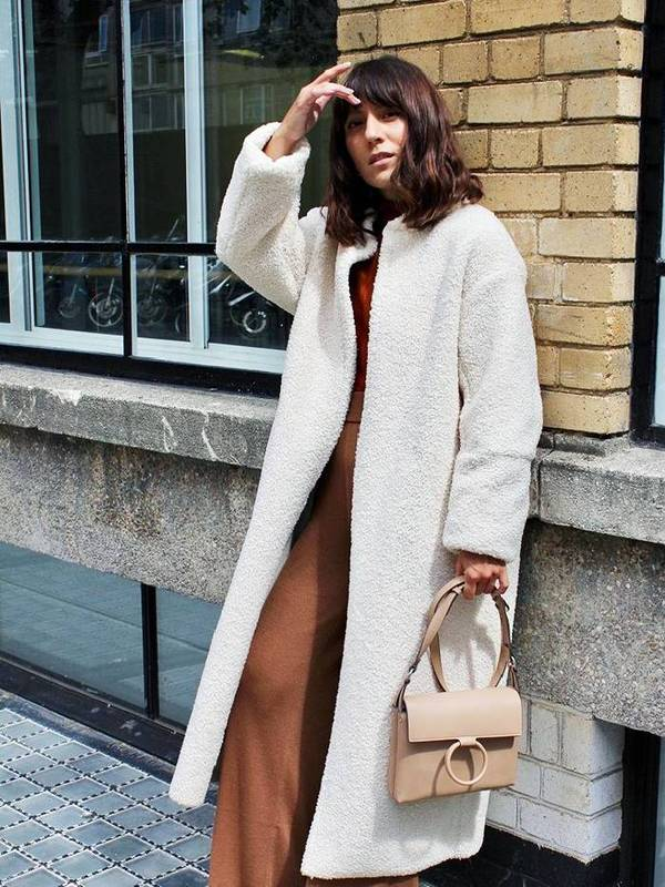 a rust-colored pantsuit, a white textural coat and a tan bag with a ring for a 70s inspired look