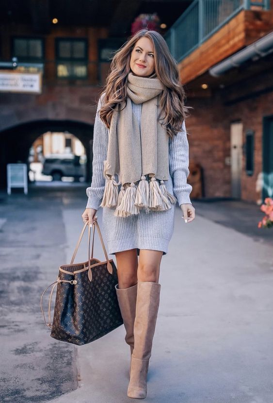 a short grey sweater dress, tan knee boots, a tan scarf with oversized tassels and a black bag