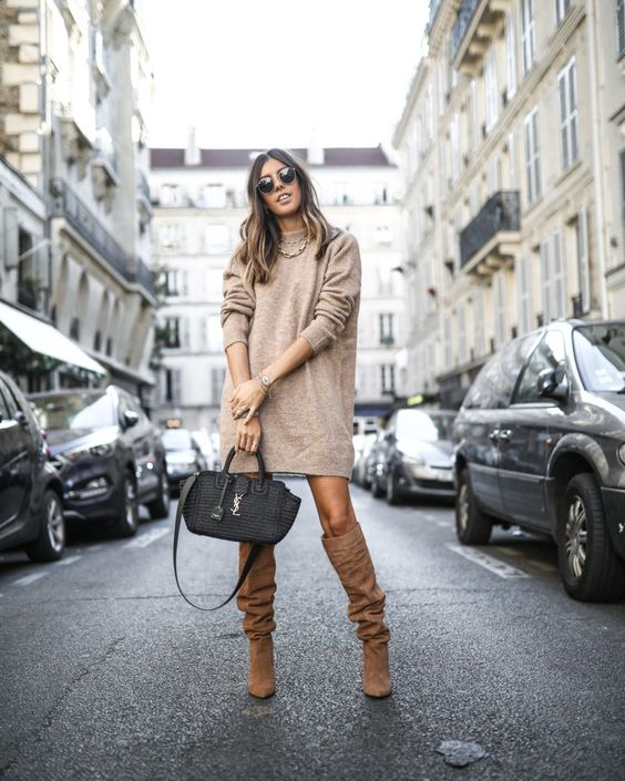 a tan mini sweater dress, brown boots, a black bag for a bold winter look