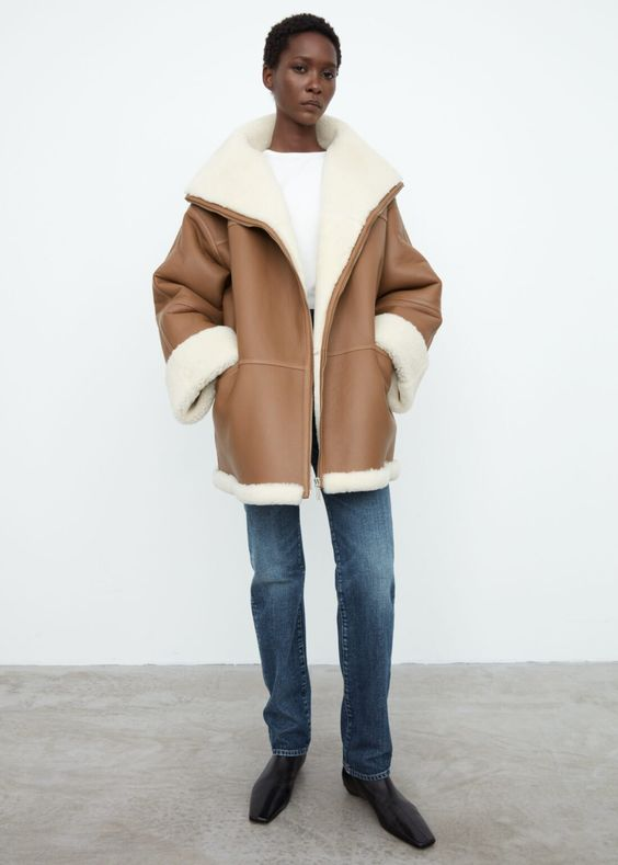 a tan short shearling coat with white fur, with an oversized silhouette is a stylish outerwear piece
