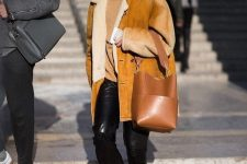 a tan top, black leather pants, black boots, an amber shearling coat and a brown bag with a minimalist handle