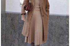 a tan turtleneck, a tan pleated midi skirt, grey boots, a brown midi coat and a brown bag