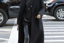 a total black outfit with a hoodie, leggings, trainers, a coat and a bag by Hailey Biber