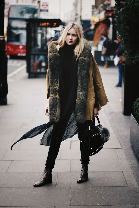 a total black outfit with skinnies, a sweater, dark snakeskin print boots and a mustard shearling coat with much fur