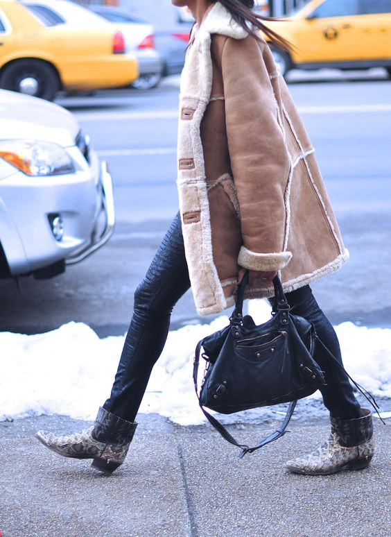 a vintage-style tan shearling coat with white fur, skinnies, and snakeskin print boots for a bold winter look