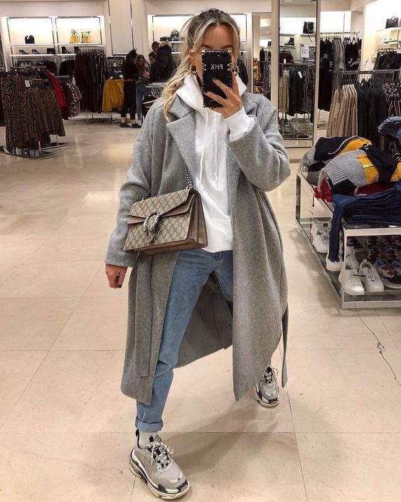 a white hoodie, blue jeans, a grey coat, grey trainers and a printed bag for a comfy winter outfit