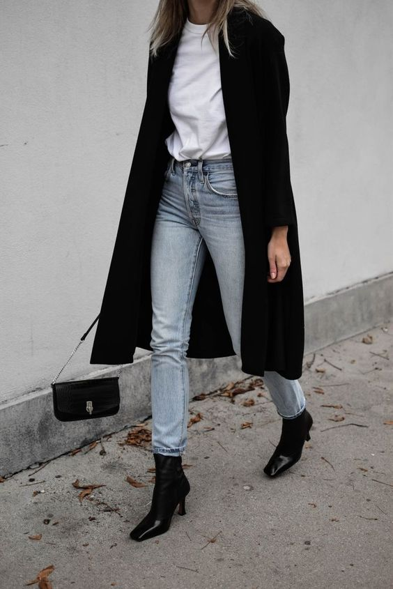 a white tee, blue skinnies, black square toe booties, a black midi coat and a black bag