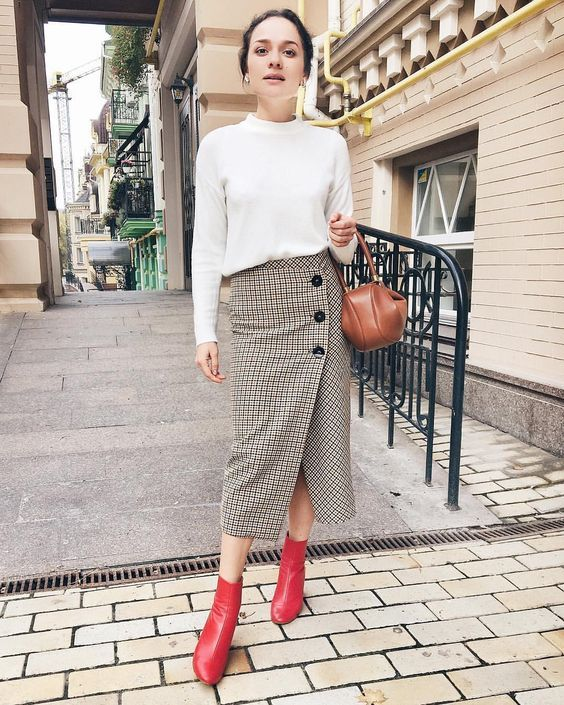 a white top with long sleeves, a tweed button midi, red boots and a brown mini bag