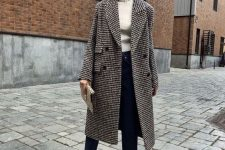 a white turtleneck, navy straight jeans, tan cutout booties, a clutch and a plaid midi coat
