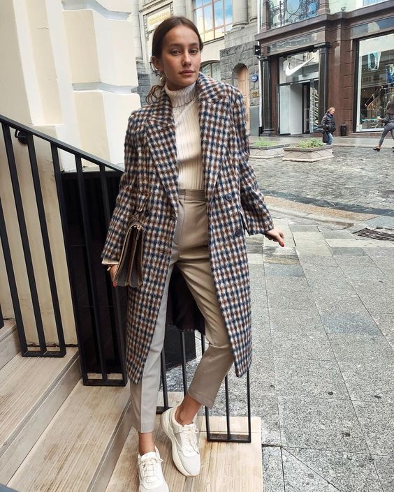 a white turtleneck, tan pants, white trainers, a bright plaid midi coat and a bag