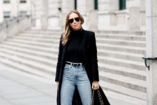an everyday look with a black turtleneck, blue jeans, sock boots, a black midi coat and a bag