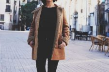 black skinnies, a black top, burgundy shoes and a brown shearling coat with faux fur