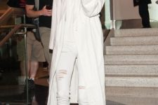 Kendall Jenner wearing a white cashmere hoodie, white skinnies, a white coat and tan booties