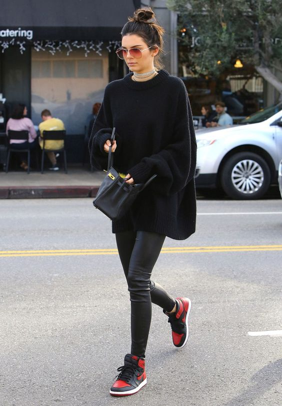 Kendall Jenner wearing black leather leggings, an oversized sweater, a black bag and black and red trainers