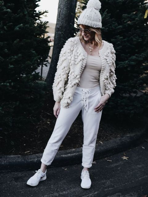 With beige top, white cropped sporty pants, hat and white sneakers