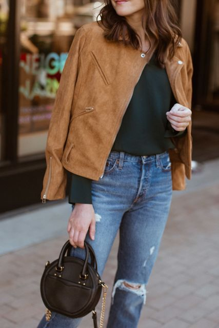 With black loose shirt, distressed jeans and black leather rounded bag