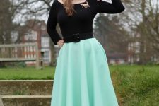 With black shirt, black belt, mint green midi skirt and printed shoes