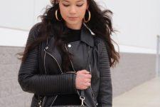 With black shirt, black leather jacket, embellished bag and skinny jeans
