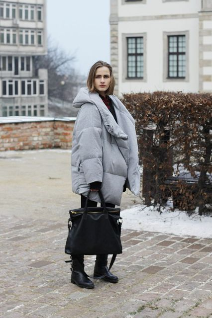 With black shirt, black tote bag, flat boots and pants