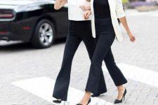 With black shirt, white long blazer and black pumps