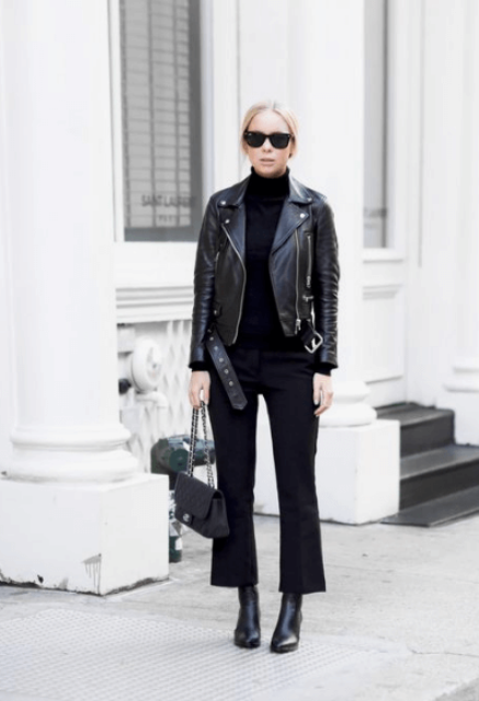 With black turtleneck, chain strap bag and black leather boots