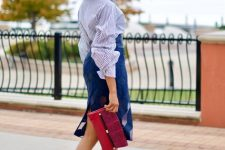 With blue printed knee-length skirt, red and marsala clutch and beige high heels