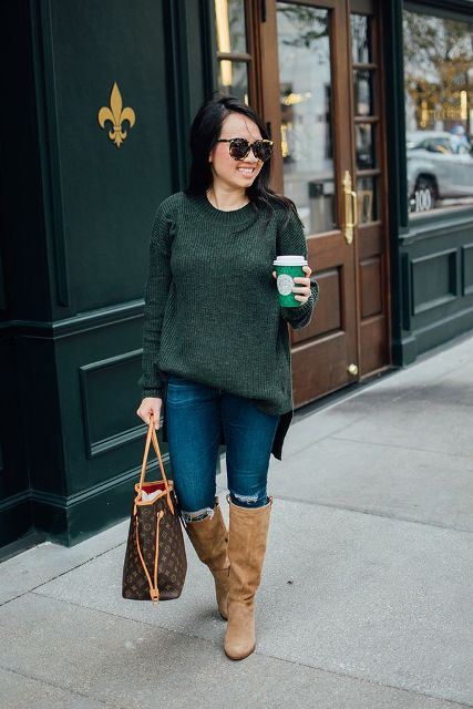 With distressed jeans, beige high boots and printed tote bag