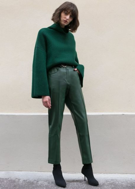 With emerald green leather cropped trousers, black high heeled boots and belt
