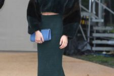 With green midi skirt, blue clutch and heeled shoes