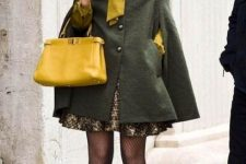 With mini dress, olive green cape coat, yellow bag and patent leather shoes