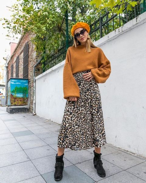 With orange beret, sunglasses, brown bell sleeved sweater and black flat boots