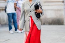 With red and pale pink pleated maxi dress, gray long blazer and clutch