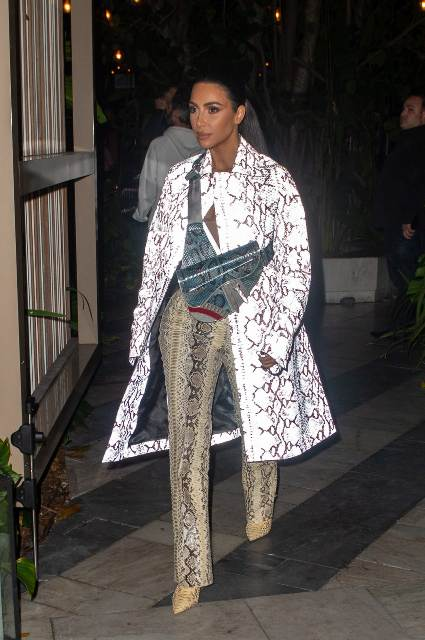 With snake print pants, boots and printed bag