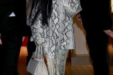 With snake printed shirt, trousers, white bag and boots