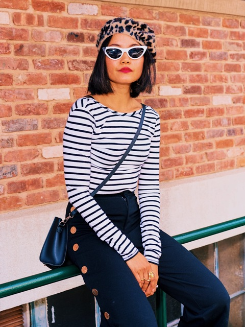 With striped long sleeved shirt, white framed sunglasses, crossbody bag and navy blue palazzo pants