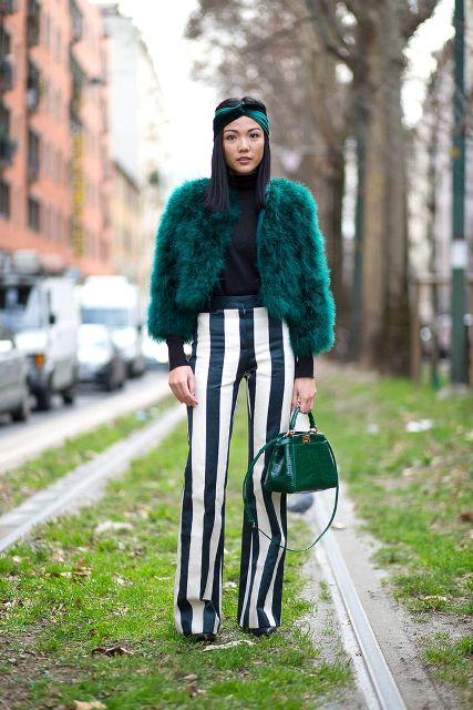 With turtleneck, striped trousers and green leather bag