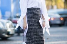 With white long sleeved shirt, printed midi skirt and unique bag