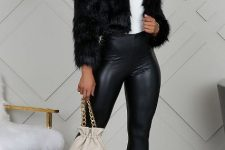 With white top, black leather skinny pants, beige bag and transparent shoes