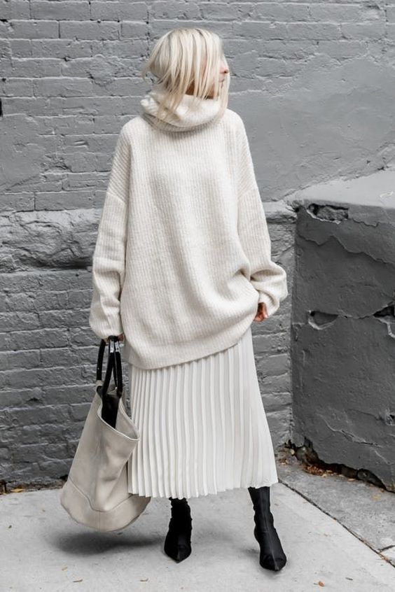 a beautiful outfit with an oversized white sweater, a pleated midi skirt, black sock boots and an oversized bag