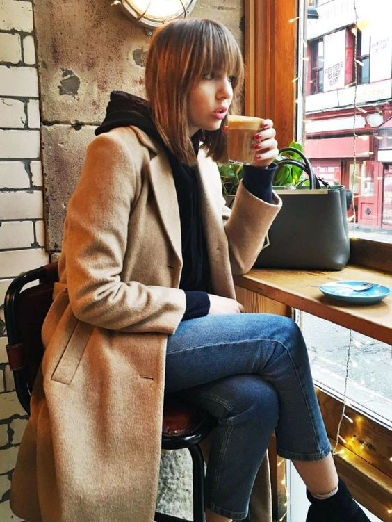 a black cashmere hoodie, a tan coat, blue skinnies, black booties and a green bag