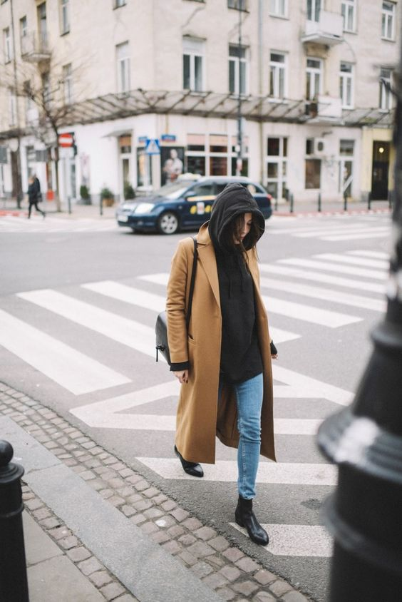 a black cashmere hoodie, blue skinnies, black boots, a tan coat and a black bag for a comfy look