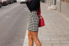 a black long sleeve top, a high waisted tweed mini skirt, black sock boots and a red crossbody bag