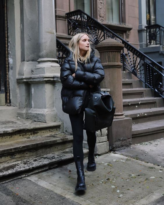 a black outfit with a puff coat, skinnies, Chelsea boots and an oversized backpack is chic