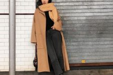 a black sweater, grey jeans, snakeskin booties, a tan midi coat, a matching scarf and a black bag