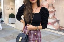 a black sweater with puff sleeves, a square cut, a burgundy tweed mini with buttons and a black bag