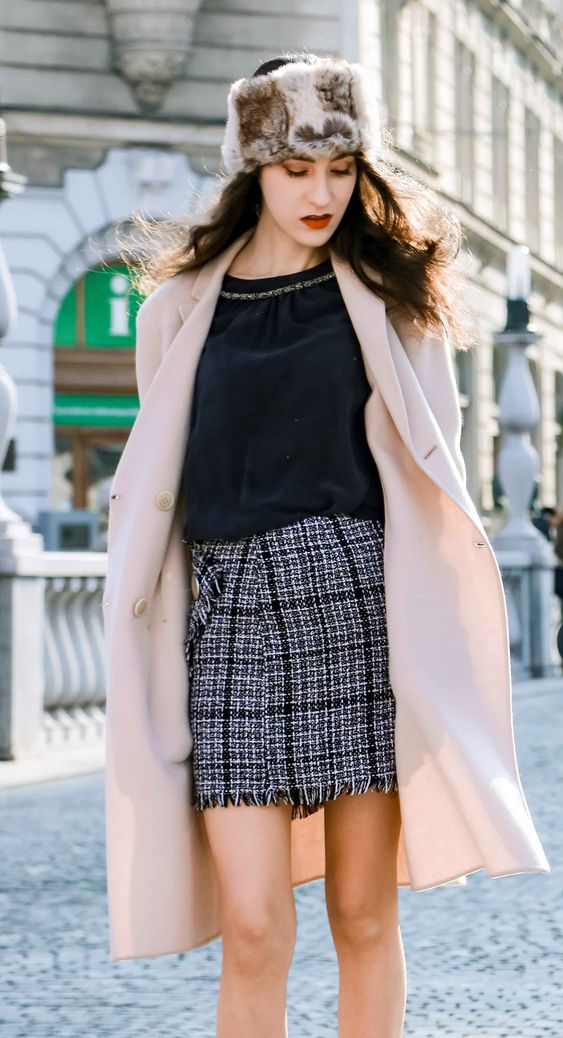 a black top, a black and grey tweed mini skirt, a blush coat and a feather hat for a winter look